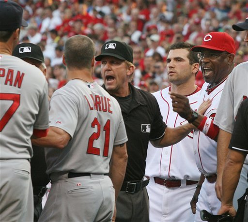 Umpire Jeff Kellogg, center, tries to keep Cincinnati Reds manager Dusty Baker, right away from memebers of the St. Louis Cardinals team during a bench clearing fight in the first inning of their baseball game in Cincinnati Tuesday Aug. 10, 2010.