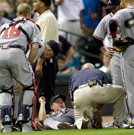 Atlanta Braves head trainer Jeff Porter, right, looks at the leg of third baseman Chipper Jones, center, as manager Bobby Cox, left, leans over during the sixth inning of a baseball game against the Houston Astros Tuesday, Aug. 10, 2010 in Houston.