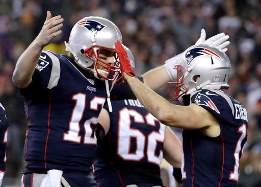 New England Patriots quarterback Tom Brady (12) celebrates with wide receiver Julian Edelman (11) after throwing a touchdown pass during the second half of the AFC championship NFL football game.