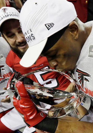 Atlanta Falcons' Deji Olatoye kisses the George Halas Trophy after the NFL football NFC championship game against the Green Bay Packers, Sunday, Jan. 22, 2017, in Atlanta.