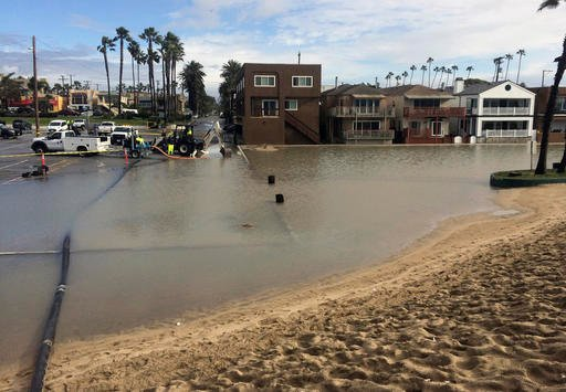 Floodwater is pumped out over a sand berm and toward the ocean in Seal Beach, Calif., on Monday, Jan. 23, 2017.