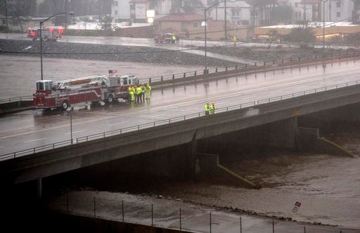 Fire units attempt to locate a possible person in Santa Ana River in Costa Mesa, Calif., during a storm Sunday, Jan. 22, 2017.