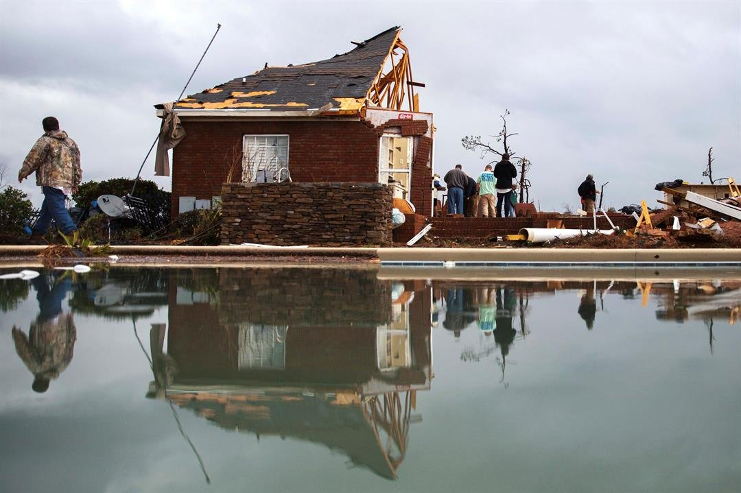 People work to clean up at a home that was damaged by a tornado in Adel, Ga. Gov. Nathan Deal declared a state of emergency in several counties, including Cook, that have suffered deaths, injuries and severe damage from storms. (AP Photo/Branden Camp)