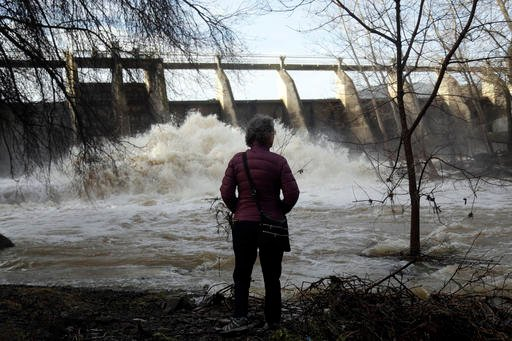 Chris Buchanan watches the overflow at a dam on Vasona Lake after a series of storms Tuesday, Jan. 24, 2017, in Los Gatos , Calif.