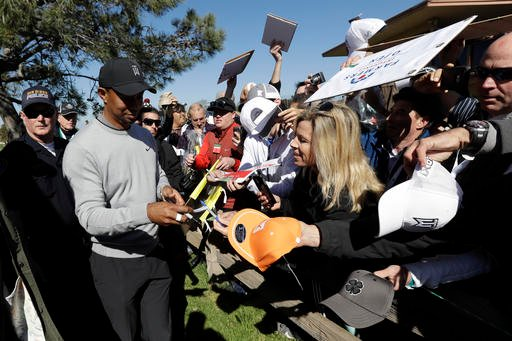 Tiger Woods, left, signs autographs after finishing his round at the Pro-Am event during the Pro-Am event at the Farmers Insurance Open golf tournament Wednesday, Jan. 25, 2017, in San Diego.