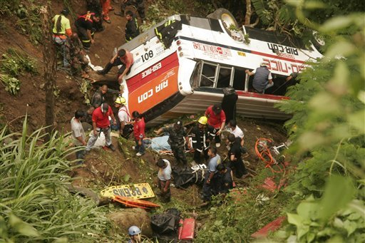 Rescuers and paramedics search for survivors after a passenger bus negotiating a downhill curve plunged off a Philippine mountain highway.