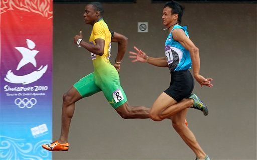 Odane Skeen of Jamaica, left, and Jirapong Meenapra of Thailand, right, compete in the boy's 100 meters at the Youth Olympics on Wednesday, Aug. 18, 2010, in Singapore. (AP Photo/Wong Maye-E)