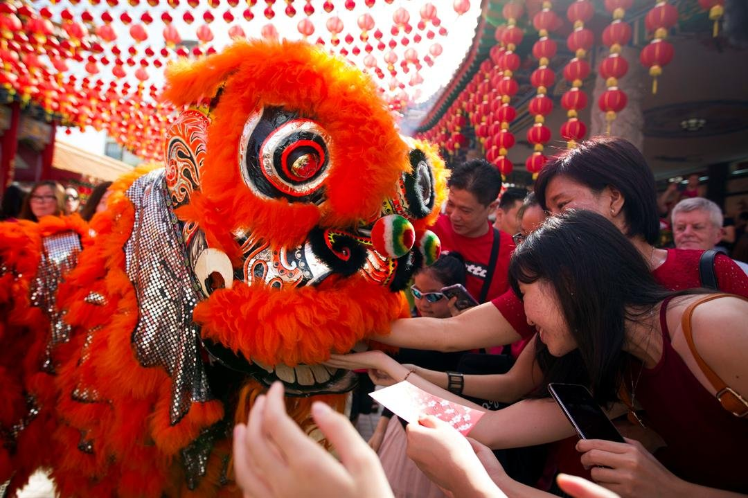 Temple visitors give red packets to the lion dance troupe during the lion dance performance on the first day of Chinese Lunar New Year at a temple in Kuala Lumpur, Malaysia, Saturday, Jan. 28, 2017. The celebration marks the Year of the Rooster in the Chi