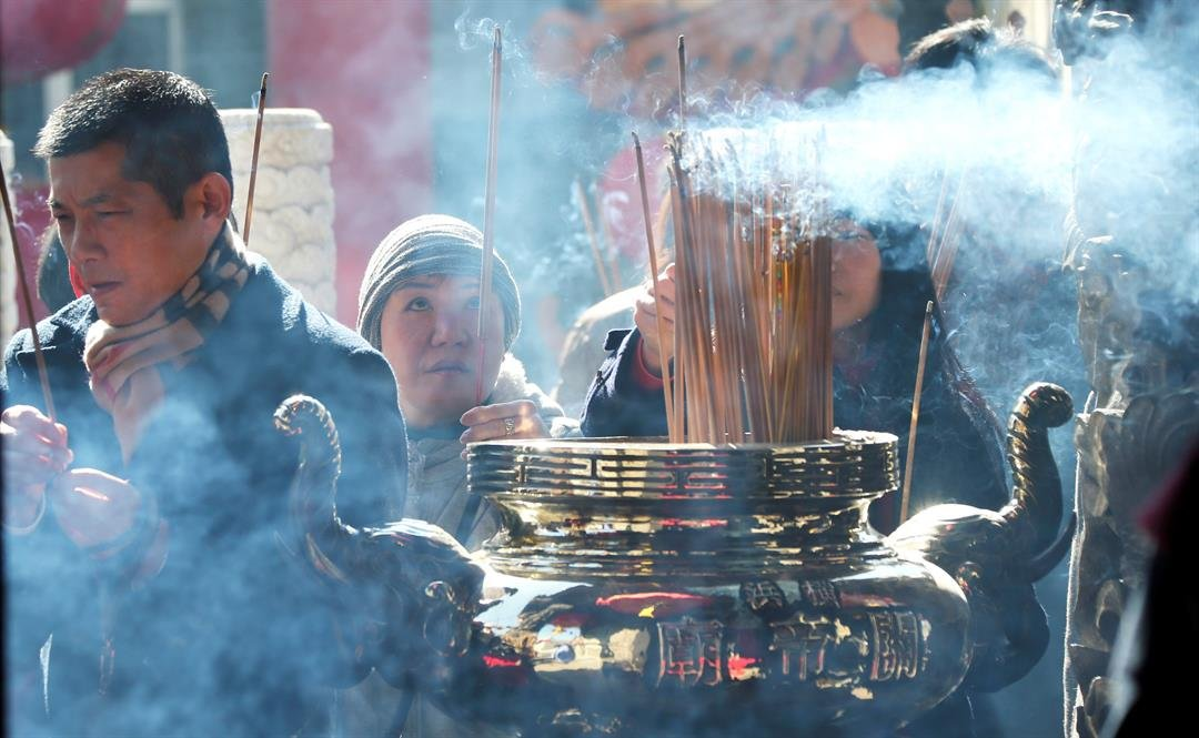 People offer prayers during celebrations of Lunar New Year at Chinatown in Yokohama, near Tokyo, Saturday, Jan. 28, 2017. Jan. 28 this year marks the Year of the Rooster in the Chinese zodiac. (AP Photo/Koji Sasahara)