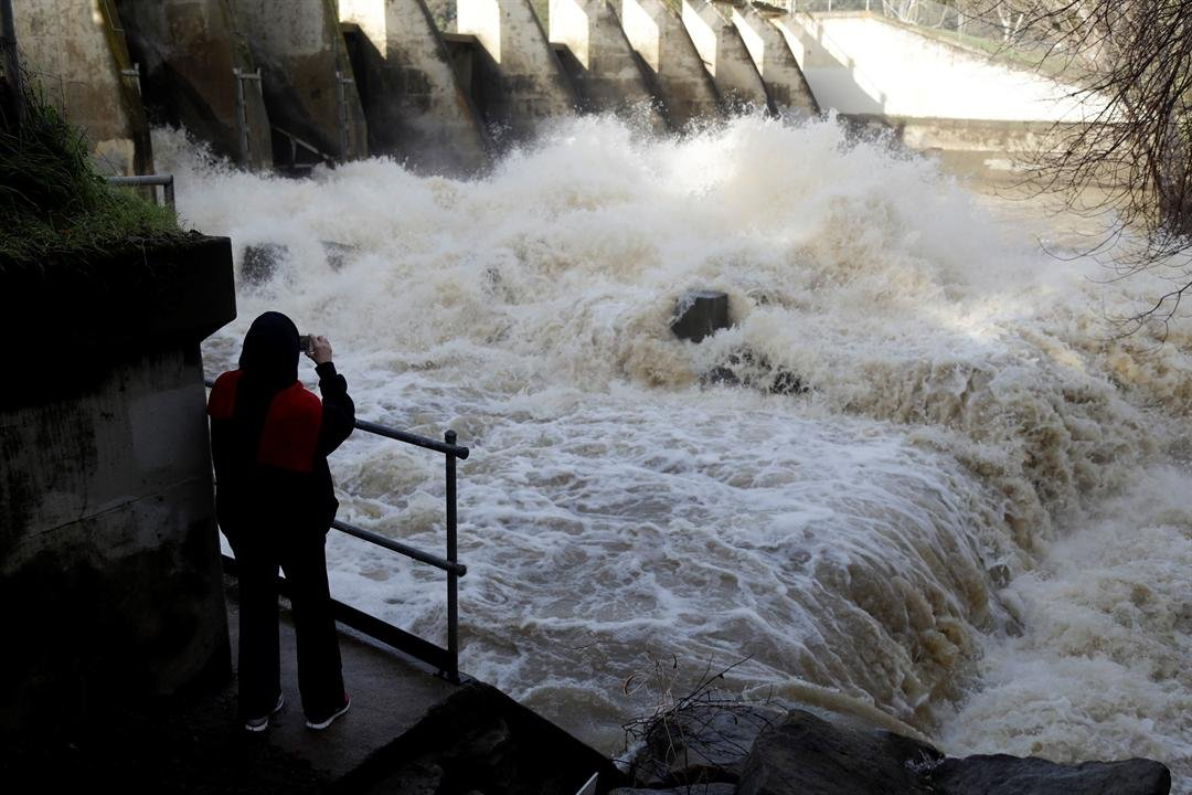 Sharon Childs takes a closer look at the overflow at a dam on Vasona Lake after a series of storms Tuesday, Jan. 24, 2017, in Los Gatos, Calif. (AP Photo/Marcio Jose Sanchez)