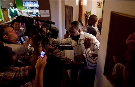 Haitian-born singer and presidential candidate Wyclef Jean, right, exits a hotel room after Haiti's Electoral Council rejected his presidential candidacy in Port-au-Prince, Haiti, Friday, Aug. 20, 2010. (AP Photo/Ramon Espinosa)