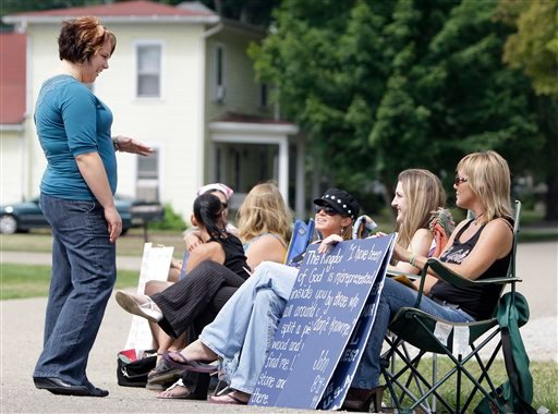 Supporters of The Fox Hole strip club protest against New Beginnings Ministries Church as Amanda Johnson, left, a member of the church, talks with them.