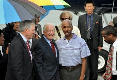 In this photo released by China's Xinhua news agency, former U.S. President Jimmy Carter, center left, poses with American Aijalon Gomes, center right, at Pyongyang airport, North Korea, on Friday Aug. 27, 2010.