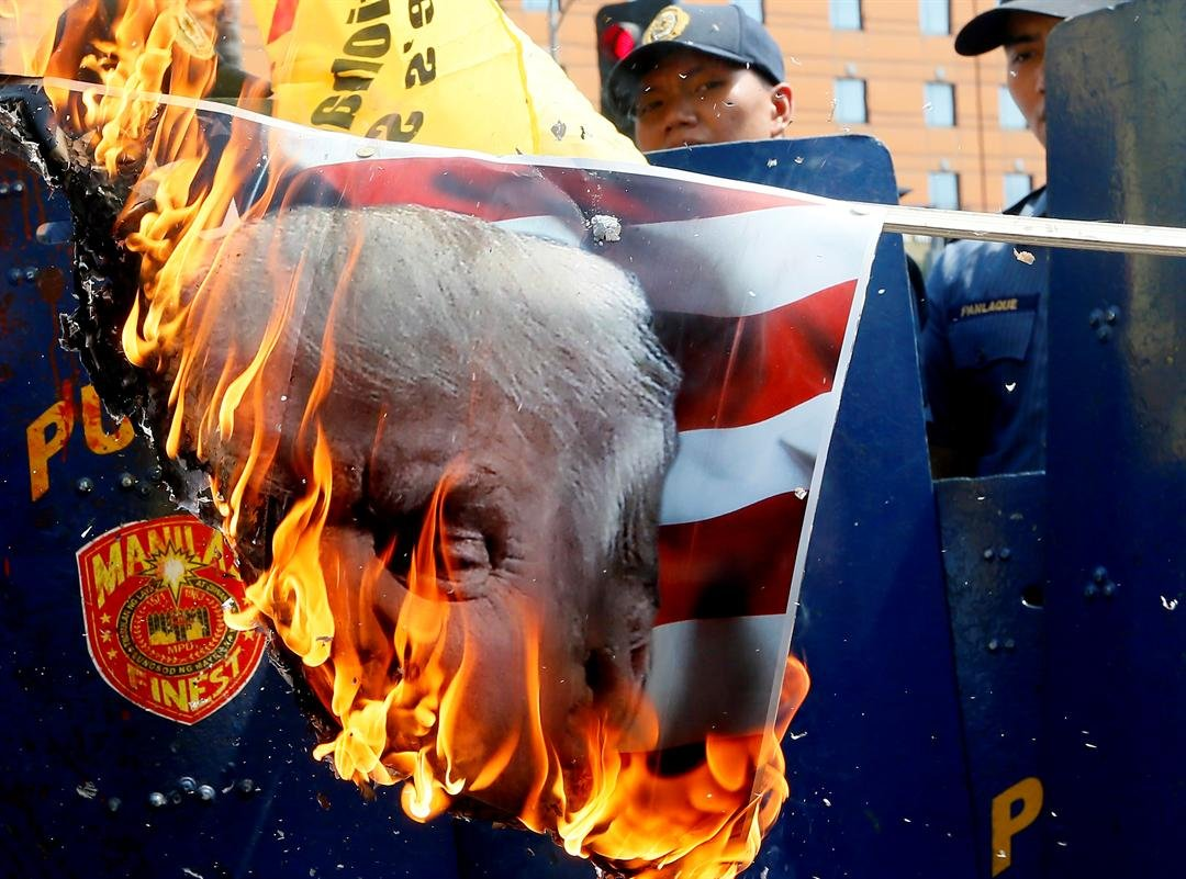 Protesters burn a portrait of U.S. President Donald Trump during a rally at the U.S. Embassy to mark the Feb. 4, 1899, Filipino-American War, Saturday, Feb. 4, 2017 in Manila, Philippines. The protesters scored Trump on his anti-immigration stance. (AP Ph