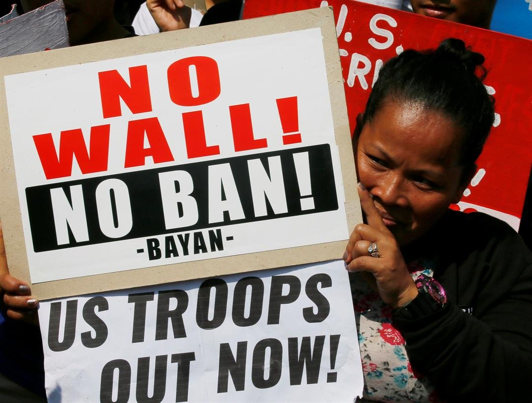 protester displays placards in front of riot police during a rally at the U.S. Embassy to protest U.S. President Donald Trump's recent anti-immigration policies, Saturday, Feb. 4, 2017, in Manila, Philippines. The protest also marked the Feb. 4, 1899 Fil