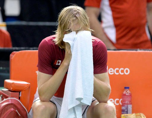 Canada's Denis Shapovalov looks on from behind a towel after a match was declared forfeited by umpire Arnaud Gabas, of France, after Gabas was hit in the face with a ball fired by Shapovalov.