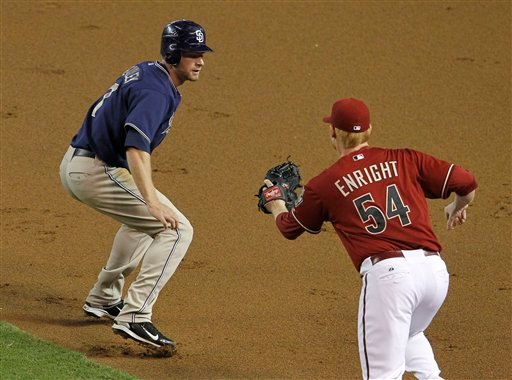 San Diego Padres' Chase Headley, left, gets caught in a rundown as Arizona Diamondbacks' Barry Enright closes in to tag him out during the second inning of a baseball game Wednesday, Sept. 1, 2010, in Phoenix. (AP Photo/Ross D. Franklin)