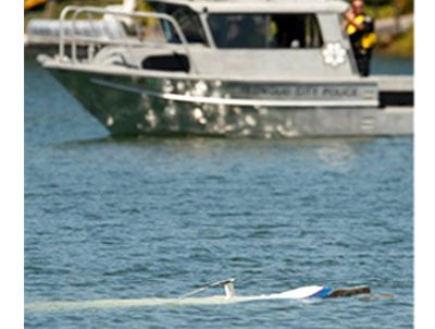 Police officials look at a small plane in the water in Redwood City, Calif., Sept. 2, 2010. Officials say a 40-year-old woman was found dead next to the wreckage of a small plane that crashed in a lagoon off San Francisco Bay. (AP Photo/Paul Sakuma)