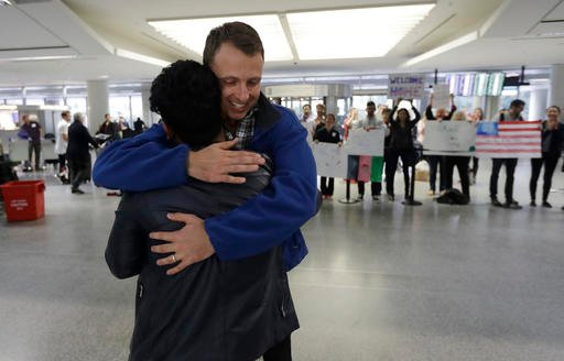 Army Capt. Matthew Ball, right, hugs his former interpreter Qismat Amin, as Amin arrives from Afghanistan, at San Francisco International Airport Wednesday, Feb. 8, 2017, in San Francisco.