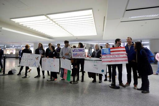Supporters wait for U.S. Army interpreter Qismat Amin to arrive from Afghanistan at San Francisco International Airport Wednesday, Feb. 8, 2017, in San Francisco.
