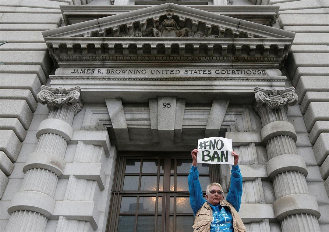 Karen Shore holds up a sign outside of the 9th U.S. Circuit Court of Appeals in San Francisco, Tuesday, Feb. 7, 2017. (AP Photo/Jeff Chiu)