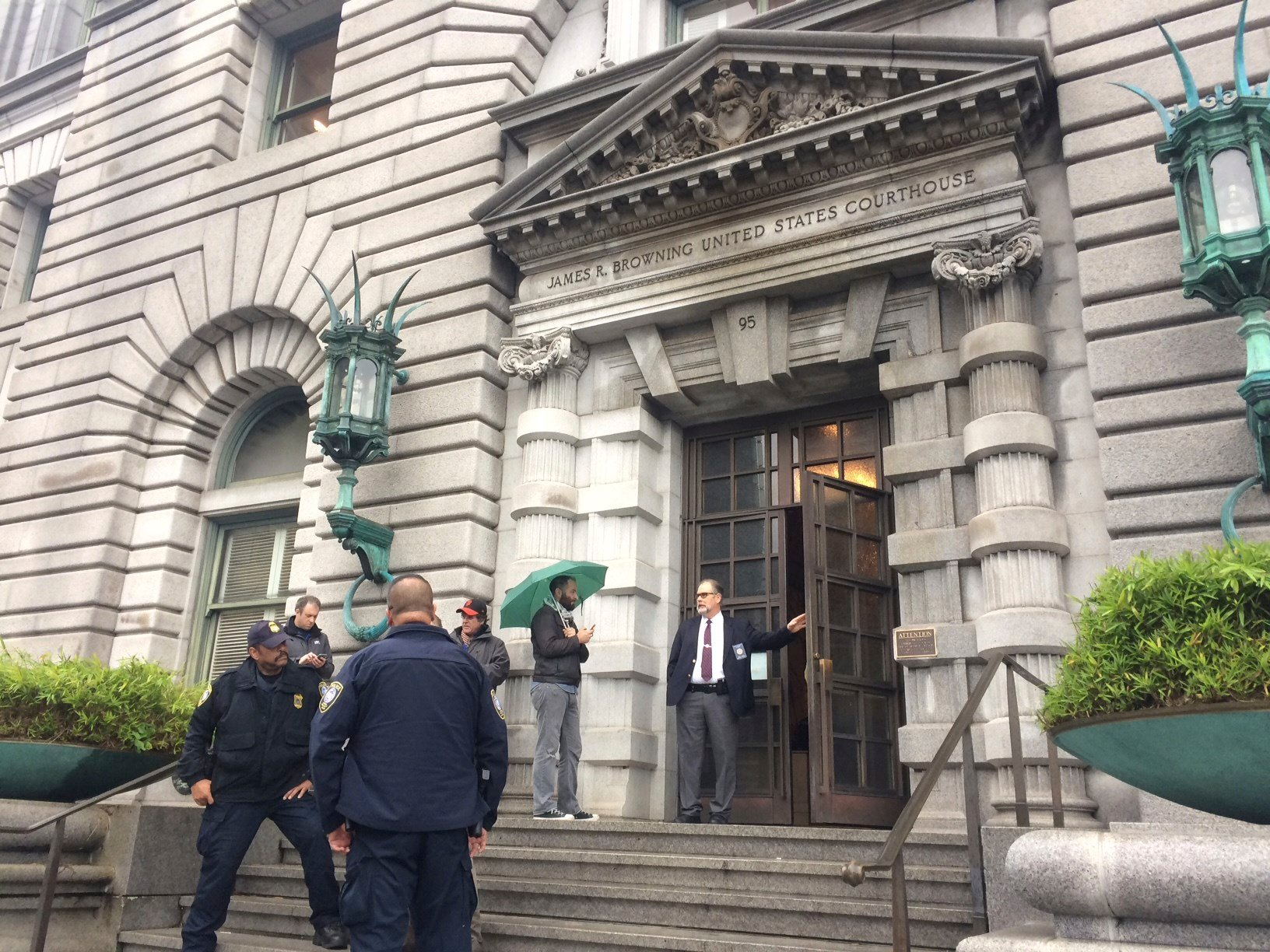 Security officers are seen outside the 9th U.S. Circuit Court of Appeals building in San Francisco on Thursday, Feb. 9, 2017