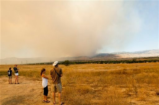 Kurt Rieder, in white hat, with his 9 year old daughter Lily watch the smoke plume from a wildland fire burning in the Four Mile Canyon area just west of Boulder Colo. on Monday, Sept. 6, 2010. (AP Photo/Peter M. Fredin)