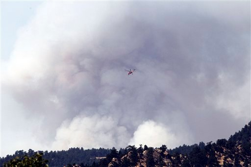 A firefighting helicopter flies over a plume of smoke from a wildfire west of Boulder, Colo., on Tuesday, Sept. 7, 2010. (AP Photo/Ed Andrieski)