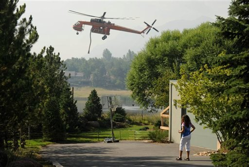 Sivia Viggiano watches from a friend's home as a helicopter flies in to load up with water at Wonderland Lake in order to work a wildfire outside of Boulder, Colo. on  Sept. 8, 2010. (AP Photo/ Matt McClain)