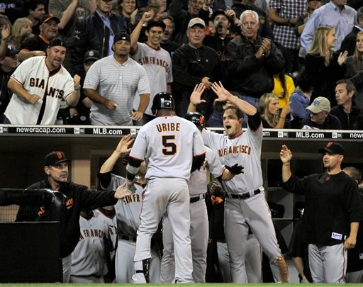 San Francisco Giants' Juan Uribe celebrates his solo home run in the dugout against the San Diego Padres during the fourth inning of a baseball game in San Diego, Thursday, Sept. 9, 2010. (AP Photo/Chris Carlson)