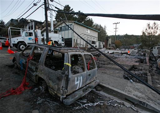 A burned car is shown in a neighborhood damaged by a gas explosion as power crews work at restoring power in San Bruno, Calif., Friday, Sept. 10, 2010. (AP Photo/Eric Risberg, Pool)