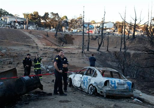Police and officials stand near a ruptured gas pipe and burned car in a neighborhood damaged by a gas explosion in San Bruno, Calif., Friday, Sept. 10, 2010. (AP Photo/Eric Risberg, Pool)