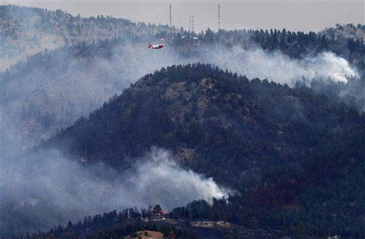 A tanker flies through smoke as a wildfire burns outside of Boulder, Colo. on Wednesday Sept. 8, 2010 .(AP Photo/Matt McClain)