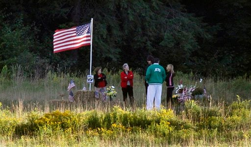 The family and friends of Flight 93 passenger John Talignani share a moment at the crash site near the temporary Flight 93 memorial in Shanksville, Pa., at sunset on Friday, Sept 10, 2010. (AP Photo/Gene J. Puskar)