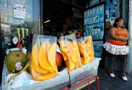 A street vendor sells fruit on Thursday, Sept. 9, 2010, in Los Angeles. (AP Photo/Damian Dovarganes)