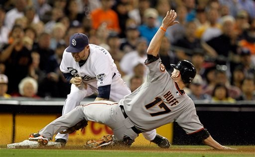 San Francisco Giants' Aubrey Huff is safe at third after San Diego Padres third baseman Chase Headley fails to make tag on a hit by Jose Guillen during the seventh inning of a baseball game in San Diego, Friday, Sept. 10, 2010. (AP Photo/Chris Carlson)