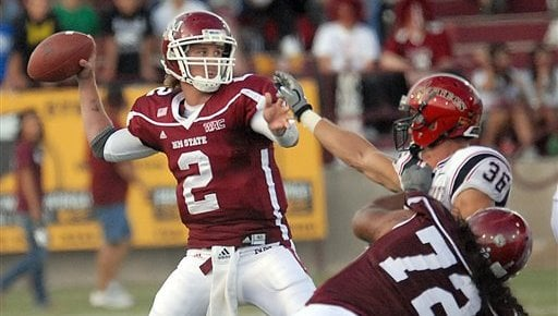 New Mexico State University's Quarterback Matt Christian looks to make a pass while Nick Tenhaeff of San Diego State Aztec, tries to get a hand in his face. (AP Photo/Las Cruces, Sun-News, Robin Zielinski)