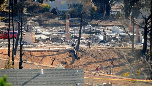 An emergency worker walks through an area of burned homes in San Bruno, Calif., on Saturday, Sept. 11, 2010. (AP Photo/Noah Berger)