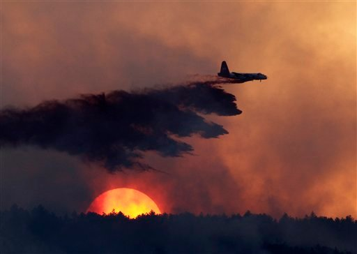 A slurry bomber drops retardant on a burning ridge as the sun sets behind it as a wildfire burns west of Loveland, Colo., on Sunday, Sept. 12, 2010. (AP Photo/Ed Andrieski)