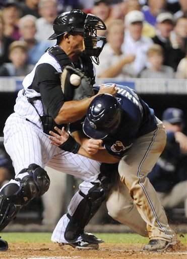 San Diego Padres' Aaron Cunningham (28) collides with Colorado Rockies catcher Miguel Olivo at home plate during the third inning of a baseball game in Denver, Monday, Sept. 13, 2010. Cunningham was out on the play. (AP Photo/Jack Dempsey)