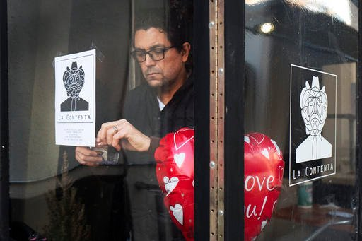 Luis Arce Mota, the chef and co-owner of La Contenta, posts a flyer in the window announcing the closure of his restaurant for the day, Thursday, Feb. 16, 2017, in New York.