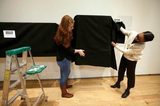 In this Wednesday, Feb. 15, 2017 photo, Wellesley College students Hannah Augst, of Richmond, Va., left, and Somé Louis, of Charlottesville, Va., right, use a black shroud to cover a display case containing donated African art objects.