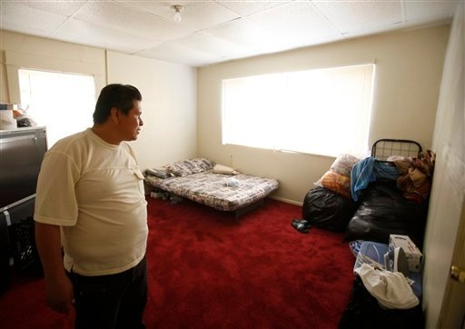 In this photo taken on Sept. 7, 2010, unemployed day worker Efren Martinez looks at bags with unsold clothing he failed to sell at swap meets, at his empty apartment bedroom in the Westlake district of LA. (AP Photo/Damian Dovarganes)
