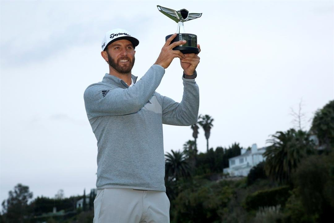 Dustin Johnson poses with his trophy on the 18th green after winning the Genesis Open golf tournament at Riviera Country Club on Sunday, Feb. 19, 2017, in the Pacific Palisades area of Los Angeles. (AP Photo/Ryan Kang)