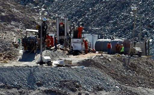 Men work on a new drill to be used in the rescue operation of 33 trapped miners at the San Jose mine in Copiapo, Chile, Monday, Aug. 30, 2010. (AP Photo/Roberto Candia)