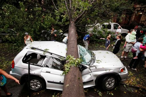 Residents in the Park Slope neighborhood in the Brooklyn borough of New York circle around a car crushed by a fallen tree, Thursday, Sept. 16, 2010. A brief but severe storm has swept through New York City, uprooting trees and damaging cars.