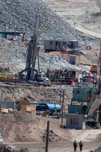 Two policemen walk next to the drill that is being used in the rescue operation of thirty-three miners trapped at the San Jose mine in Copiapo, Chile, Friday, Sept. 17, 2010.