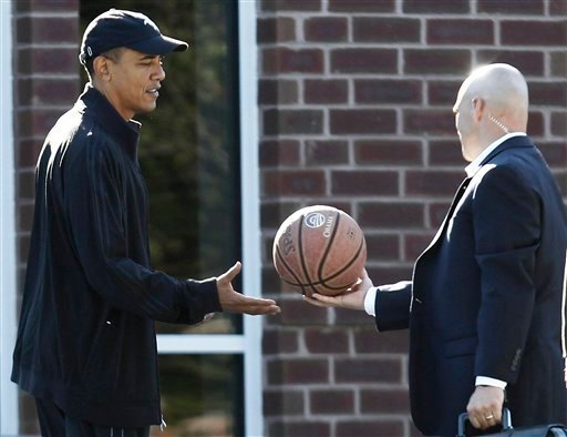 President Barack Obama is handed a personalized basketball by a military aide as he arrives for a private game of basketball at Fort McNair in Washington, Saturday, Sept. 18, 2010. (AP Photo/Charles Dharapak)