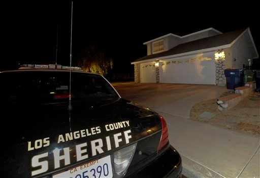 """A Los Angeles County Sheriffs officers sit outside Reyna Chicas' home the possible leader of a """"cult-like"""" group who has been reported missing along with 12 other members, Saturday, Sept. 18, 2010, in Palmdale, Calif. (AP Photo/Gus Ruelas)"""