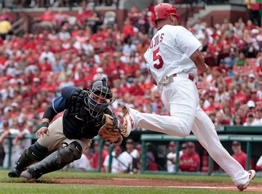 St. Louis Cardinals' Albert Pujols, right, is safe at home as he avoids the tag from San Diego Padres catcher Yorvit Torrealba on a sacrifice fly by Pedro Feliz during the first inning of a baseball game Sunday, Sept. 19, 2010, in St. Louis. (AP Photo)